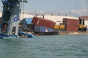 """Coast Guard crewmembers photographed tumbling shipping containers at Port-au-Prince Jan. 13, 2010. Coast Guard personnel arrived in Haiti to assess damage to the ports and waterways after an earthquake ravaged the island Jan. 12, 2010. U.S. Coast Guard photo."" (Text From U.S. Coast Guard)"